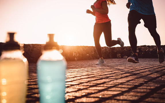 Young fit couple jogging at sunset outdoor - Sporty people doing run workout session next the sea - Healthy, wellness and sport activity lifestyle concept