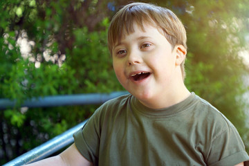 Portrait of a laughing boy with down syndrome while playing in a park