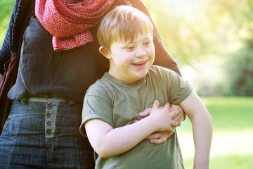 Little boy with down syndrome cuddling up to his mother in a park