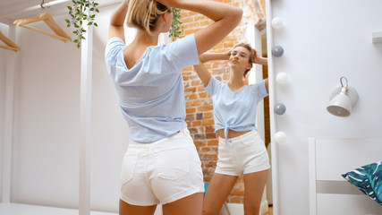 Woman trying clothes and looking at mirror smilng happy.