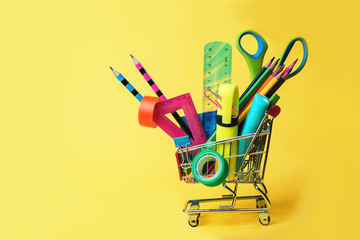 Back to school concept with shopping cart and colorful pencils, square ruler, scissors, clips, markers on pastel yellow backdrop. Flat lay, top view, copy space. Wall mural