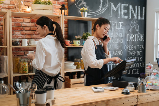 Beautiful skilled entrepreneur dressed in apron with mock up making coffee business with partner. barista standing at bar counter and talking on cellphone with web consultant order food in cafeteria