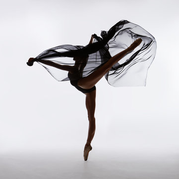 A ballerina dances with a black cloth