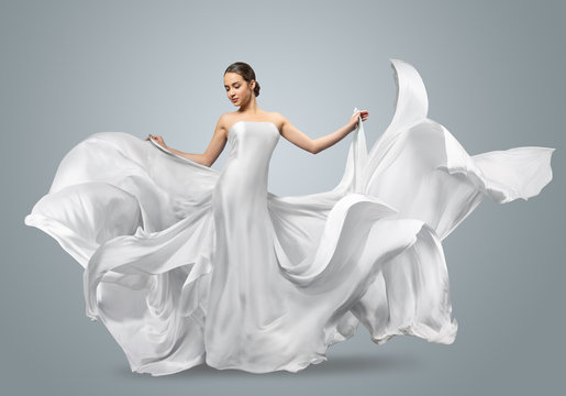 Fashion portrait of a beautiful woman in a waving white dress. Light fabric flies in the wind.