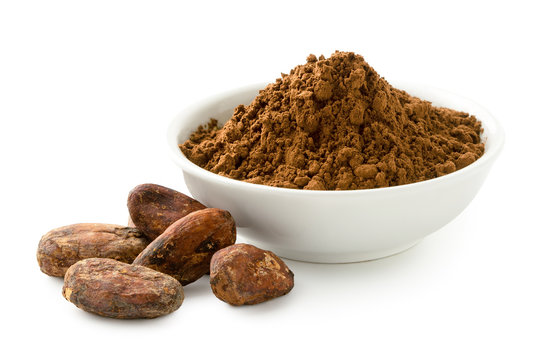 Cocoa powder in a white ceramic bowl next to roasted unpeeled cocoa beans isolated on white.