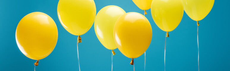 bright party yellow balloons on blue background, panoramic shot