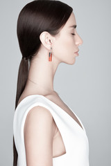 Young trendy female with earring with orange gemstone