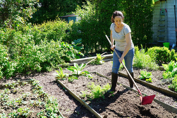 Woman at gardening works with plow in flower beds