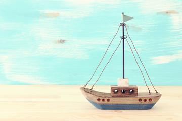 vintage boat over wooden table or shelf and pastel blue background