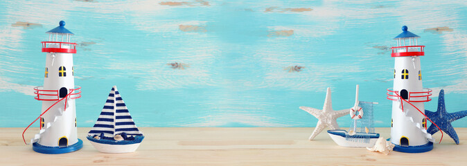 vacation and summer concept with vintage boat, starfish, lighthouse and seashells over wooden table or shelf infront of pastel blue background. banner