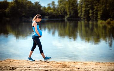 Sport pour femme enceinte : les activités à privilégier Pregnant woman walking at lakeside, sport during pregnancy