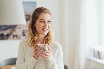 schöne junge frau mit einer tasse tee in ihrer wohnung