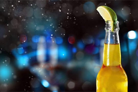 Cold beer with lime on background