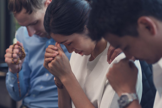Christian men put hand on woman shoulder  for encouragement and  praying  to God and  hoping for better, Group of christian concept