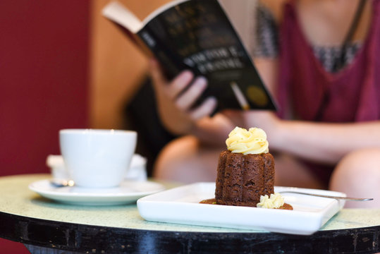 cake with a cup of coffee and someone reading a book