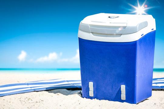 Summer time on beach and blue beach fridge on sand. Ocean landscape and sunny day.