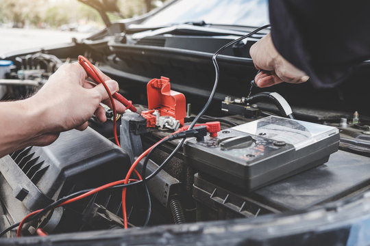 Services car engine machine concept, Automobile mechanic repairman hands checking a car engine automotive workshop with digital multimeter testing battery, car service and maintenance