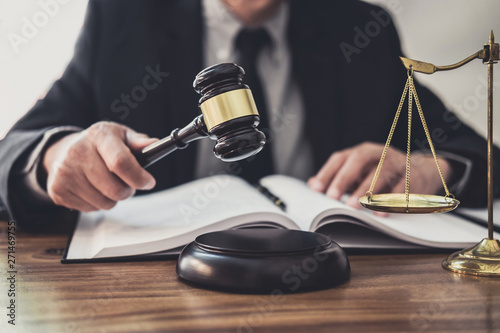 Male lawyer or judge working with contract papers, Law books