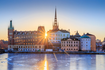 In de dag Stockholm Riddarholmen - part of the historical Old Town (Gamla Stan) in Stockholm, Sweden, at sunrise in winter. Sun star is directly behind the islet and ice is formed on the frozen lake water surrounding it.