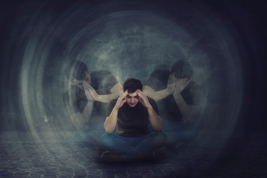 Man seated on the floor, hands to head, suffer split emotions into different inner personalities. Multipolar mental health disorder. Schizophrenia psychiatric disease.