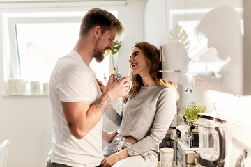 cute caucasian couple spending their morning, drinking in the kitchen