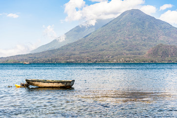 Moored boat on lake with Toliman & Atitlan volcanoes behind at Lake Atitlan, Guatemala