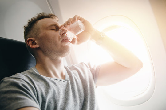 Man drinks water in an airplane before takeoff. Concept lays ears