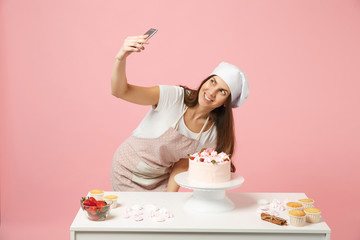 Chef cook confectioner or baker in apron white t-shirt, toque chefs hat cooking cake at table doing selfie shot on mobile phone isolated on pink pastel background in studio. Mock up copy space concept