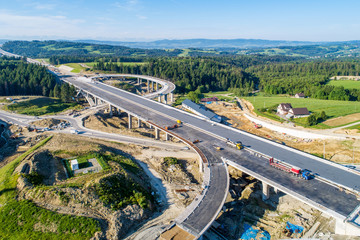 Fototapeta New highway under construction in Poland on national road no 7, E77, called Zakopianka.  Overpass crossroad with traffic circles and viaducts near Naprawa village. Aerial view in June 2019 obraz
