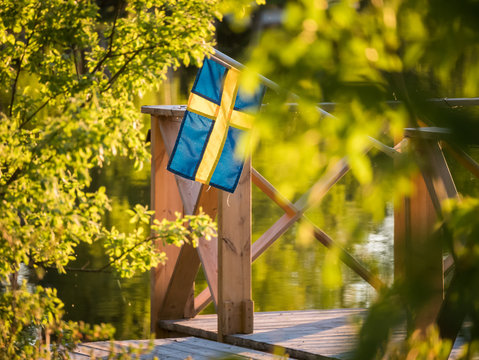 Swedish flag on a floating dock in summer sunset light in Sweden.