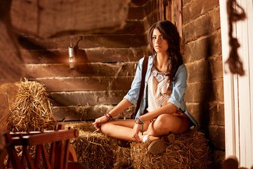 Sensual woman on hay in barn, agriculture. Woman with long brunette hair on dried grass, farm. Agriculture, farm, harvest. Eco tourism, agritourism, rural vacation. Beauty, fashion, country lifestyle