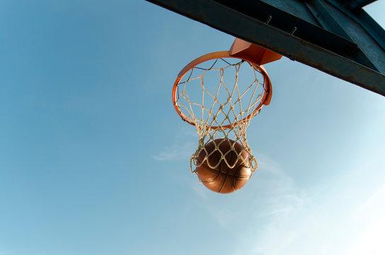 Basketball ball going through a hoop, beautiful natural lighting at sunset