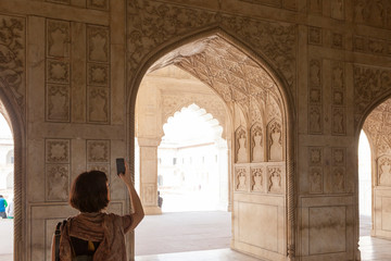30 years old girl taking photo with smartphone in Agra Fort, India