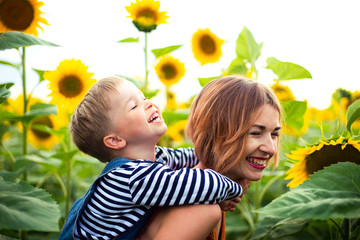 Woman standing in the sunflower field, holding her son on her back.