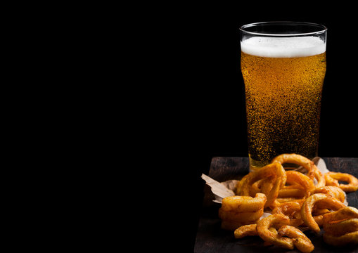 Glass of lagger beer with curly fries snack on vintage wooden board on black background. Space for text