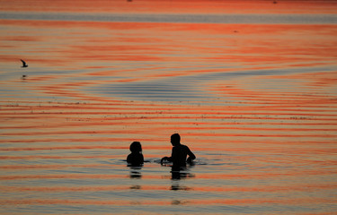 People enjoy sunset in a lake on the outskirts of Minsk