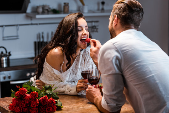couple with glasses of red wine at wooden table with bouquet of roses, man feeding woman with strawberry