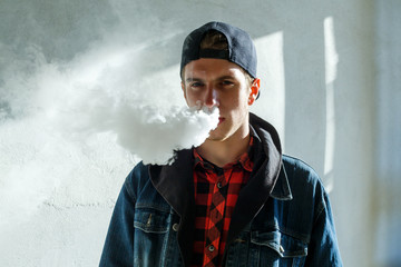 Vape teenager. Portrait of young handsome guy in a cap smoking an electronic cigarette on the street in the spring. Bad habit that is harmful to health. Vaping activity. Close up.