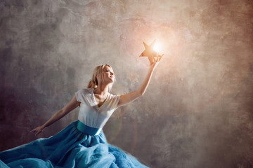 Shining star in hand, reach for the dream concept. Young woman holding a star in her hand Wall mural