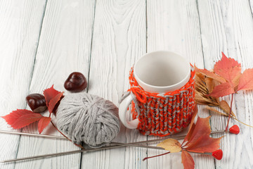 Autumn still life cup of coffee on wooden table. nitted sweater with autumn leaves, spokes, crochet and coffee mug. Autumn moody style background. Top view.