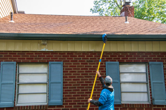 Young man cleaning the soffit of a one story house with a brush on a long pole. The house has blue shutters.