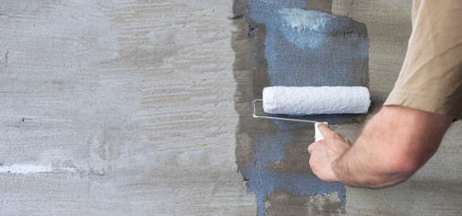 Priming the wall with a paint roller. Builder's hand with paint roller close-up. Panoramic photo....