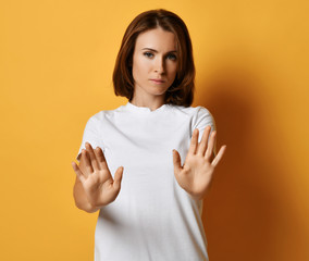 Woman in white t-shirt tries to stop something shows Stop sign gesture with her arms putted out