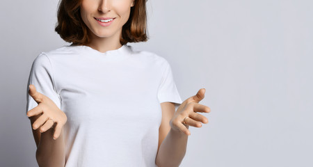 Young smiling woman stands with her hands with open palms like she is holding a big bowl or something on white
