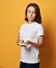 Woman in white t-shirt and blue jeans looks at a bundle of money banknotes cash she holds