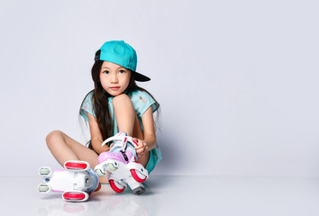 Little asian baby girl kid sitting with roller skates in light blue t-shirt and hat cap happy smiling on white