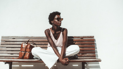 A young pensive African female in sunglasses and white trousers is enjoying the summer sun while sitting on the wooden bench outdoors in front of a white wall, with a leather bag next to her