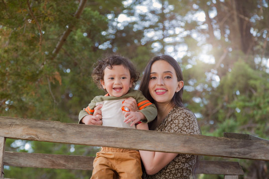 Portrait of mom and son playing in a tree house smiling and having fun - Hispanics