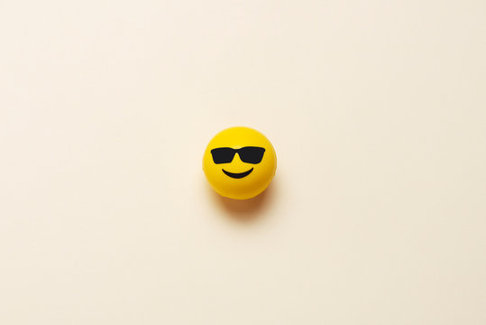 Smiling emoticon ball with sunglasses