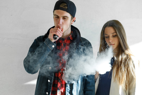 Vape teenager. Young cute girl in casual clothes and handsome guy in a cap smoke an electronic cigarette outdoors. Bad habit that is harmful to health. Vaping activity.